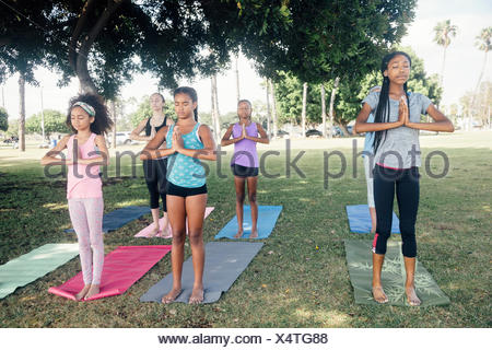 Girls and teenage schoolgirls practicing yoga mountain pose on school playing field - Stock Photo