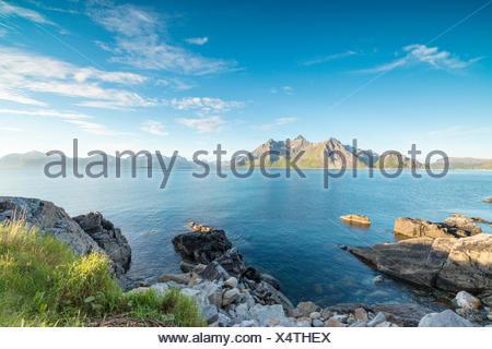 Sun shines on the blue sea and the rocky peaks at night during summer Vikten Nord Trøndelag Lofoten Islands Norway Europe - Stock Photo