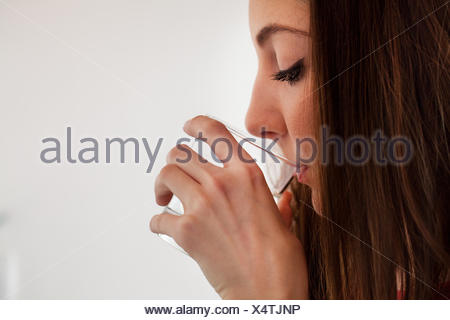 Young adult woman sipping water from glass - Stock Photo