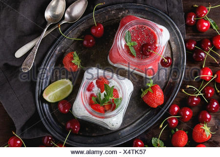 Two Square glass jars with homemade yogurt with mint, strawberry puree, cherry and chia seeds served on vintage tray with fresh - Stock Photo