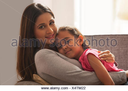 Daughter resting on her mothers chest - Stock Photo