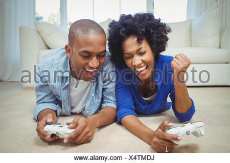 Smiling couple lying on the floor - Stock Photo