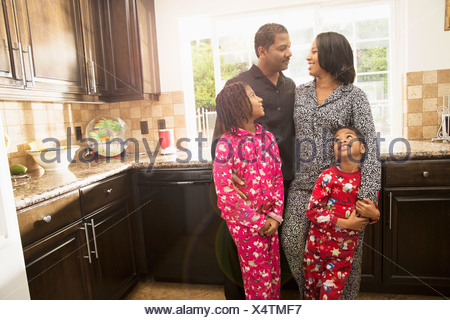 Mid adult couple with son and daughter in kitchen - Stock Photo