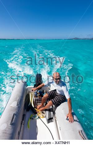 Man in dinghy on Caribbean Sea - Stock Photo
