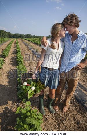 Maryland USA couple walking vegetable plants holding hands - Stock Photo