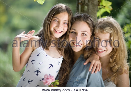 Three girls hugging each other - Stock Photo