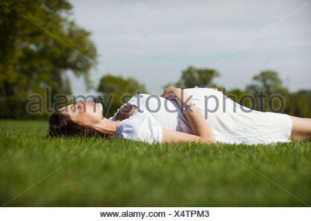 Pregnant woman lying on grass - Stock Photo