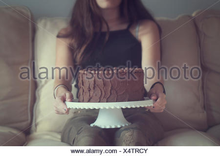 Girl holding chocolate cake on a cake stand - Stock Photo