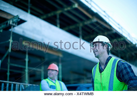 Construction workers talking on site - Stock Photo