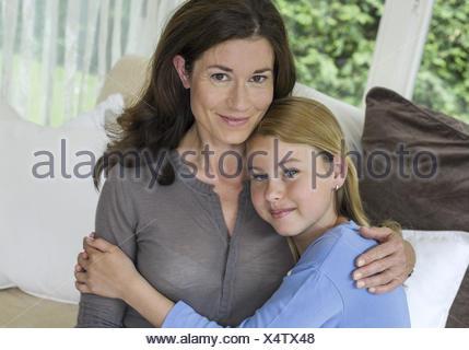Mutter sitzt mit Tochter auf Sofa umarmen sich (model-released) - Stock Photo
