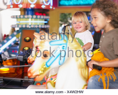 Little girls on merry go round. - Stock Photo