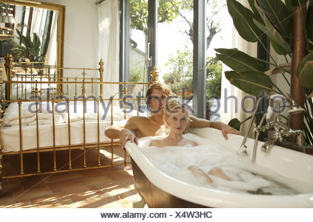 bedroom bath couple proper bath together recreation 20 30 years partnership respect love falls in love romanticism bubble bath have of a bath care personal care body hygiene enjoy rest take it easy affection tenderness erotically interior arrangement interior setup extravagant brass bed luxury inside live unusually extremely