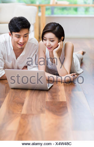 f2b8d8b610 Young couple lying on floor using laptop with a cute dog Stock Photo ...
