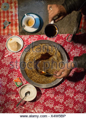 A woman cooks a meal of Maltashtze Giyaling, Hunza pancakes. - Stock Photo