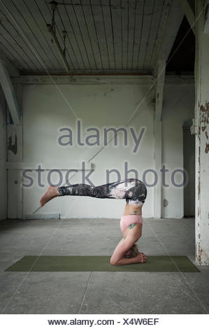 Mid adult woman practicing headstand pose in yoga studio, Munich, Bavaria, Germany - Stock Photo