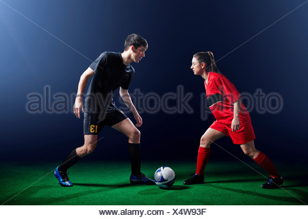 Male and female soccer players with ball - Stock Photo
