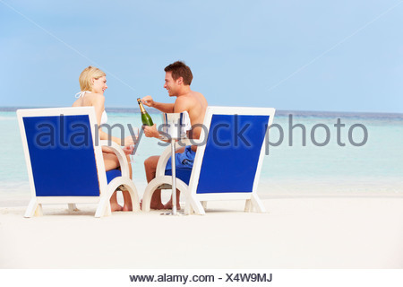 Couple On Beach Relaxing In Chairs And Drinking Chapagne - Stock Photo