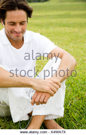 Man smiling sitting on the grass - Stock Photo