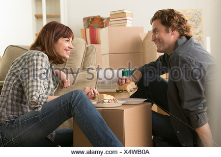 Couple having lunch break whilst moving - Stock Photo