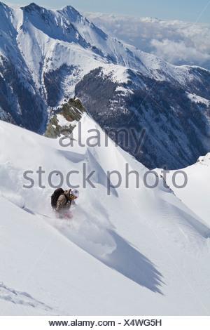 Austria, Kaprun, Kitzsteinhorn, Man skiing in powder snow - Stock Photo