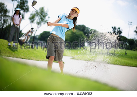 Woman playing golf with woman in background - Stock Photo
