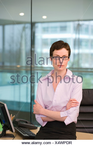 Businesswoman, with short hair and spectacles, leaning against desk in office, arms folded, portrait - Stock Photo