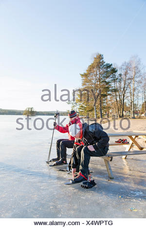 Sweden, Gastrikland, Edsken, Mature woman and man ice skating on frozen lake - Stock Photo