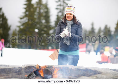 Woman warming by fire pit, Vancouver, Canada - Stock Photo