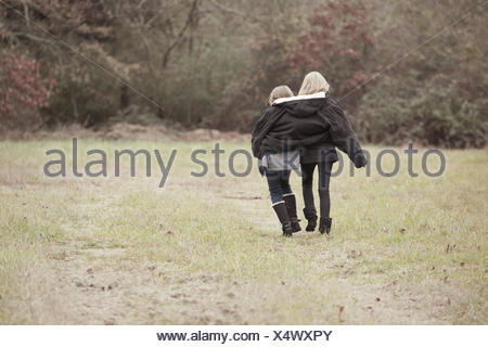 USA, Georgia, View of sisters (8-9, 12-13 years) walking together - Stock Photo