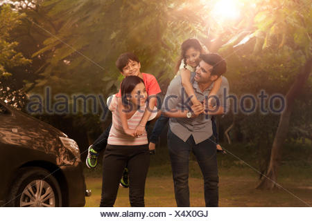 Mother and father carrying children on back in park - Stock Photo