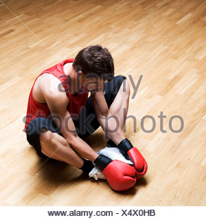 A young man wearing boxing gloves - Stock Photo