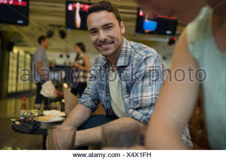 Portrait smiling young man with friends bowling alley - Stock Photo