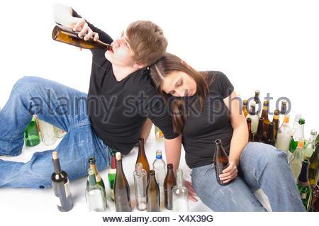 Ein junger Mann und eine junge Frau sitzen nebeneinander auf dem Fußboden inmitten von vielen leeren Flaschen. Freigestellt vor weißem Hintergrund. - Stock Photo