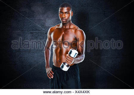Composite image of portrait of a fit shirtless young man lifting dumbbell - Stock Photo
