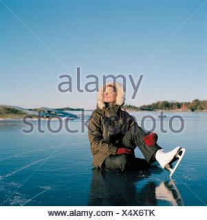Sweden, Uppland, Varmdo, Bjorno, Mid adult woman sitting on frozen lake - Stock Photo
