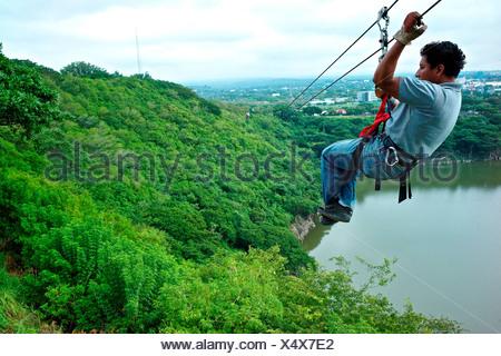 Nicaragua, Man sliding down zipline overlooking Laguna de Tiscapa at el Parque Nacional de la Loma de Tiscapa - Stock Photo