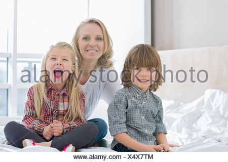 Portrait of happy mother with children in bedroom - Stock Photo