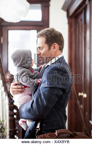 Businessman holding baby daughter - Stock Photo