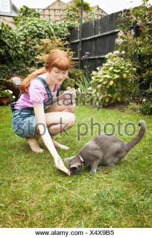 Woman feeding cat in garden - Stock Photo