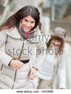 Smiling young woman climbing stairs with friend outdoors - Stock Photo