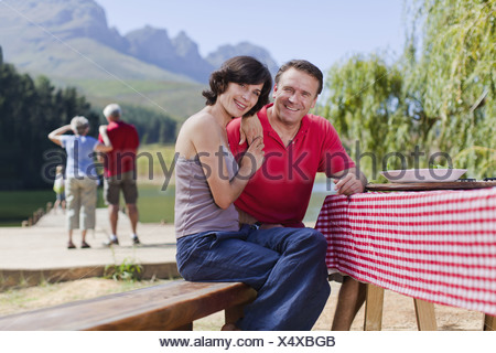 Couple sitting at picnic table together - Stock Photo