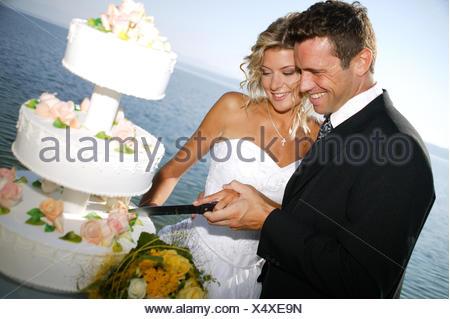 bridal couple outside, with weddingcake - Stock Photo