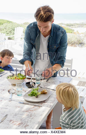 Father serving food to children on table - Stock Photo