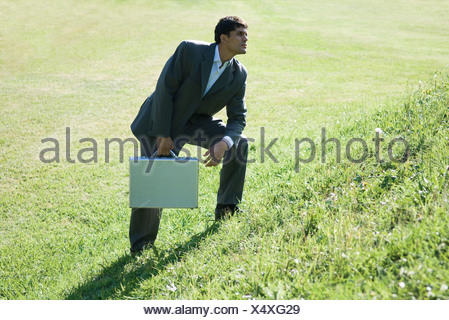 Businessman holding briefcase, standing on hill - Stock Photo