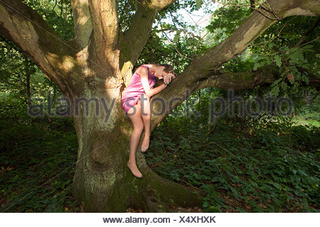 Young woman draped old oak tree - Stock Photo