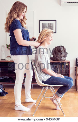 Full length side view of young woman brushing sister's hair at home - Stock Photo
