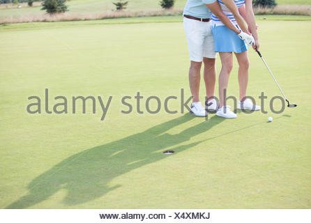 Low section of couple playing golf - Stock Photo