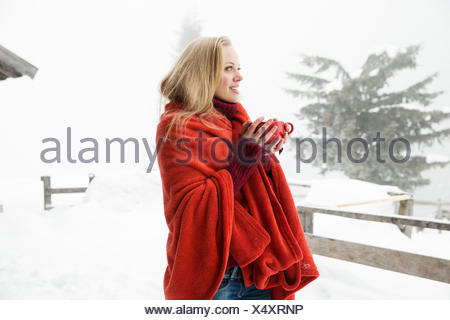 Young woman in snowy mist wrapped in red blanket drinking coffee - Stock Photo