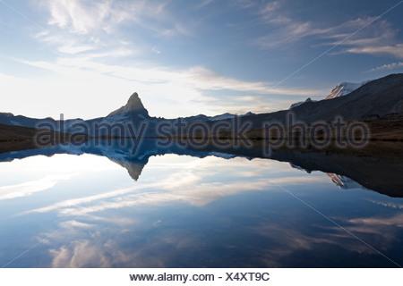 Shortly after sunset, Mt Matterhorn, Mt Klein Matterhorn and Mt Breithorn are reflected in the Stellisee Lake, Zermatt - Stock Photo
