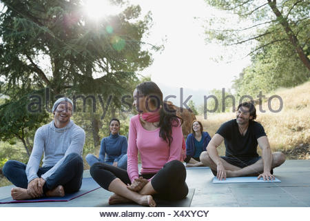 Smiling friends after yoga class on deck - Stock Photo